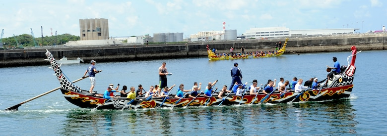 The Kadena men's dragon boat team practices rowing in sync as the Kadena women's dragon boat team passes in the distance in Naha City, Okinawa, Japan, April 12, 2014. The teams attended two dragon boat familiarization practices at the race location. (U.S. Air Force photo by Airman 1st Class Zade C. Vadnais)