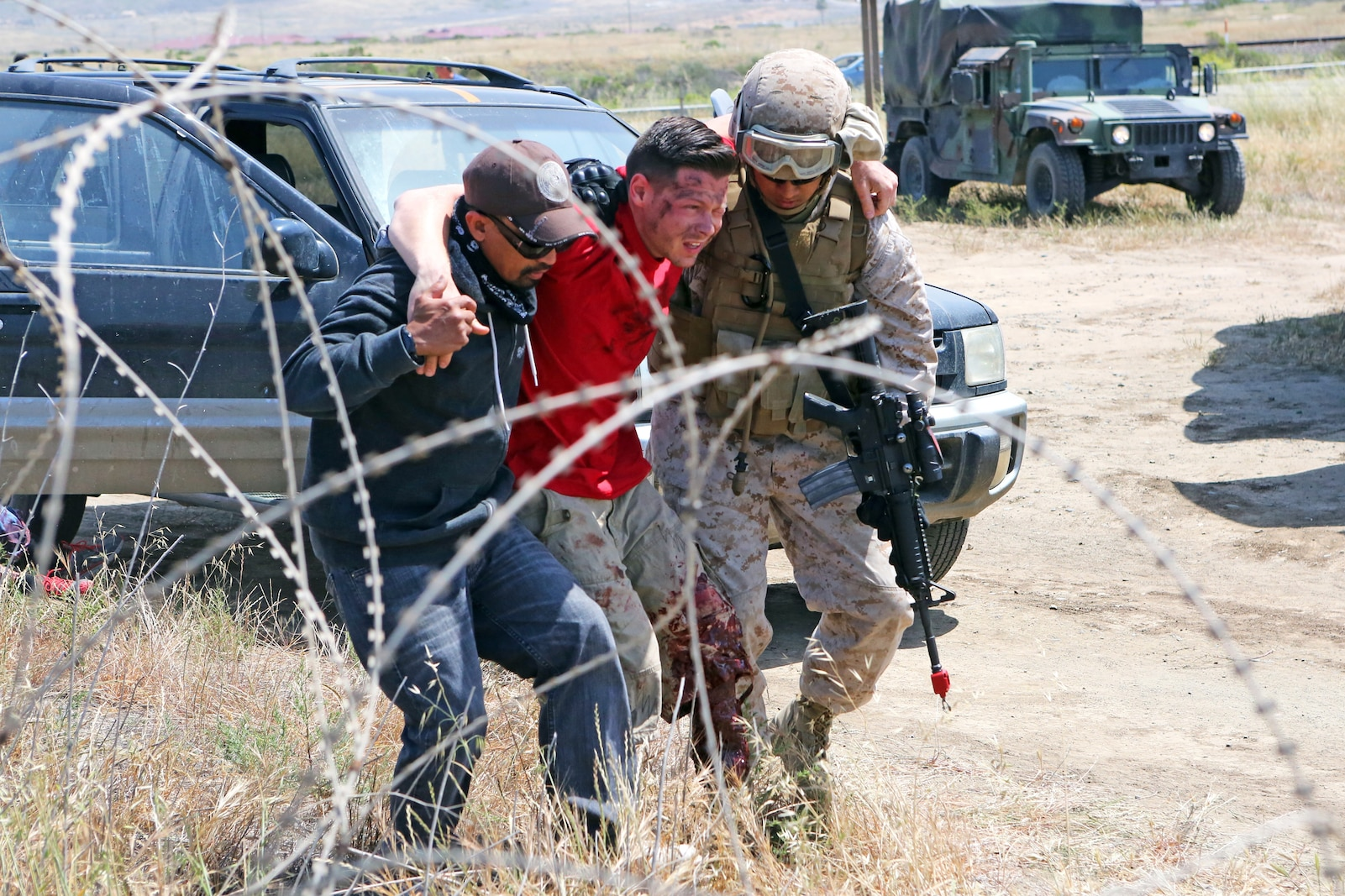 """A Marine with Combat Logistics Battalion 15, 1st Marine Logistics Group, assists """"wounded locals"""" in receiving medical aid during a mass casualty event as part of the battalion's first field training exercise of the year at Red Beach aboard Camp Pendleton, Calif., May 6-10, in preparation for pre-deployment training with the 15th Marine Expeditionary Unit this fall. This event employed the use of role players from SpecPro Technical Services aboard base who used make up to present the service members with authentic-looking injuries. The exercise allowed CLB-15 to practice procedures and protocols they will apply while acting the 15th MEU's primary logistical support element during its deployment early next year. Providing this  support to the MEU allows it to focus on its chief objective as a crisis response force, ready to respond to disaster or humanitarian relief operations."""
