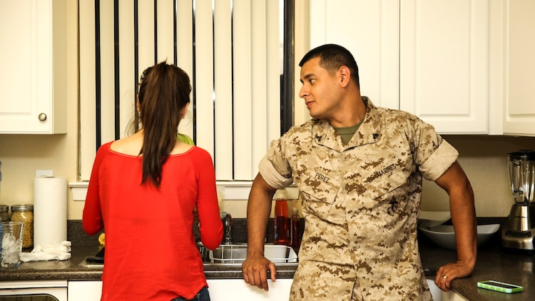 Corporal Alberto Perez III, right, administrative specialist, 15th Marine Expeditionary Unit, talks to his wife, Carla Jimenez, about his day at work aboard Camp Pendleton, Calif., May 8, 2014. Perez, 22, is from Burbank, Calif. (U.S. Marine Corps photo by Cpl. Emmanuel Ramos/Released)