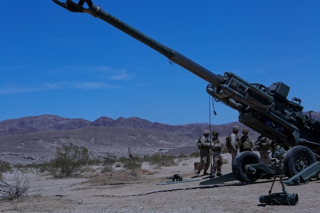 Ryan Forbes, second from left, a 13 year-old native of San Diego, talks with Marines about the M777 lightweight howitzer at Marine Corps Air Ground Combat Center Twentynine Palms May 13, 2014. Forbes was an honorary Marine for a day with Lima Battery, 3rd Battalion, 11th Marine Regiment, and learned about the weapons systems and lifestyles of the Marines. He was accompanied by his parents and brother, and attended training with the battery, participating in drills and eating lunch with a section. Forbes has wanted to join the military for several years and spends time learning about the different branches. He was diagnosed with medulloblastoma, a form of brain cancer in January. His diagnosis and current treatment for medullablastoma hasnt hampered his enthusiasm for the military.