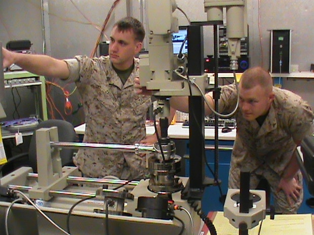 Two Marines calibrate a torque wrench using the torque standard from the Expeditionary Test, Diagnostic and Measurement Equipment Maintenance System. The ETMS lets Marines calibrate test equipment in 28 different test areas.