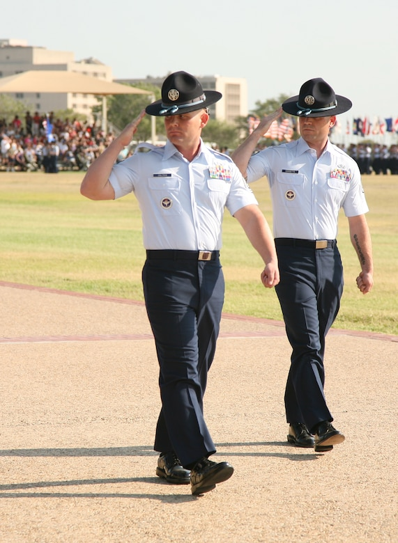 """Tech Sgt. Matthew Coltrin, former Air Force Basic Military Training Instructor, (left), performs """"eyes right"""" during his final parade as a basic military training instructor at Lackland Air Force Base, Texas, June 17, 2011. In 2006, Coltrin applied for MTI duty and throughout his years wearing his hat, he received several accolades, including the Excellence in Instruction award at Military Training Instructor School, Non-commissioned Officer of the Year, Military Training Instructor Association President's Award, and Blue Rope of the Year.  (Courtesy Photo)"""