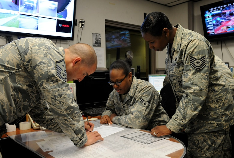 Master Sgt. Trapper Otto, 509th Security Forces Squadron first sergeant, signs an Air Force Form 2708 as Senior Airman Jamecia Smith, 509th Security Forces Squadron desk sergeant, and Tech. Sgt. Michelle Caldwell 509th Security Forces Squadron assistant first sergeant, act as witnesses at Whiteman Air Force Base, Mo., May 1, 2014. Any time security forces detains a member, the first sergeant has to sign this form. (U.S. Air Force photo by Airman 1st Class Joel Pfiester/Released)