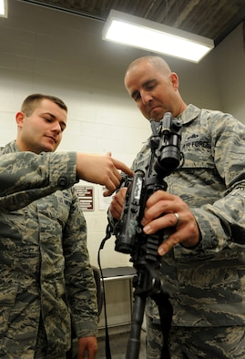 Master Sgt. Trapper Otto, 509th Security Forces Squadron first sergeant, and Senior Airman Matthew Stivala, 509th Security Forces Squadron response force member, inspect an M-4 rifle at Whiteman Air Force Base, Mo., May 1, 2014. U.S. Air Force first sergeants are responsible for the morale, welfare and well-being of the enlisted members of their respective squadrons.(U.S Air Force photo by Airman 1st Class Joel Pfiester/Released)