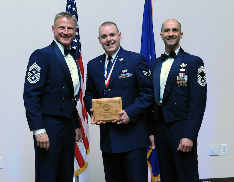 Senior Airman Craig Kortan, 460th Space Communication Squadron, center, receives the Academic Achievement Award during the Buckley Airman Leadership School Class 14-D graduation May 9, 2014, at the Leadership Development Center on Buckley Air Force Base, Colo. This award is presented to the student with the highest overall average on all academic evaluations during ALS. (U.S. Air Force photo by Airman Emily E. Amyotte/Released)
