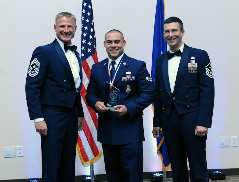 Senior Airman Vincent Rios, 460th Security Forces Squadron, center, receives the Leadership Award during the Buckley Airman Leadership School Class 14-D graduation May 9, 2014, at the Leadership Development Center on Buckley Air Force Base, Colo. This award is presented to the graduate who displays the best overall characteristics of an effective leader. (U.S. Air Force photo by Airman Emily E. Amyotte/Released)