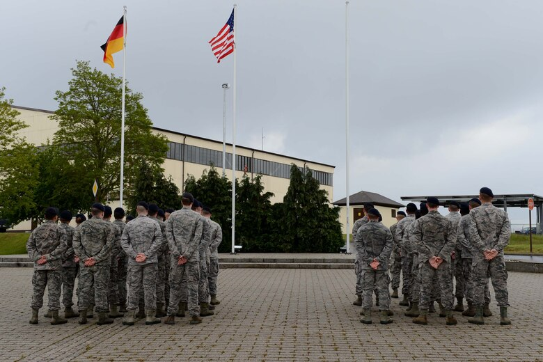 U.S. Air Force Airmen stand at parade rest during a National Police Week retreat ceremony at Spangdahlem Air Base, Germany, May 12, 2014. National Police Week is held in remembrance of fallen police officers and security forces members. (U.S. Air Force photo by Airman 1st Class Kyle Gese/Released)
