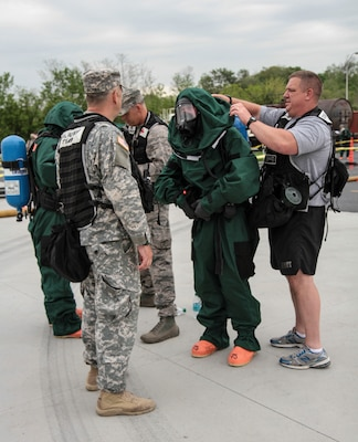 First responders from West Virginia National Guard 35th Civil Support Team help each other gear up for a practice exercise held at Harrisburg Area Community College on May 12, 2014, as part of Vigilant Guard 2014. Members of civilian and military first responder teams came together for this event which is held in different states four times a year.