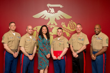 Sgt. Jason Howton (fourth from left), a recruiter assigned to Marine Corps Permanent Contact Station Port Angeles, Wash., poses with his wife and command members of Marine Corps Recruiting Command and Marine Corps Recruiting Station Seattle following an awards ceremony at MCRS Seattle, April 15, 2014. During the ceremony, Howton received a Navy and Marine Corps Achievement Medal for his exceptional contribution to MCRS Seattle's recruiting mission. Howton, 27, is from Milton, Fla.