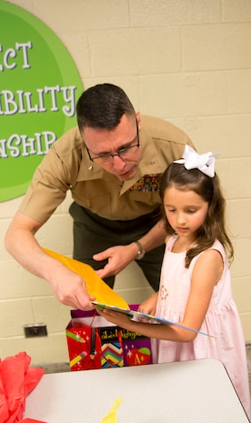 Brig. Gen. Robert Castellvi, the commanding general of Marine Corps Installations East – Marine Corps Base Camp Lejeune gives Evoli, a military child, a book after meeting her for lunch at Parkwood Elementary School in Jacksonville, N.C, May 7. Evoli won the lunch with Castellvi at a raffle held during the All-American Family Night, an event hosted by the Camp Lejeune School Liaison in April.