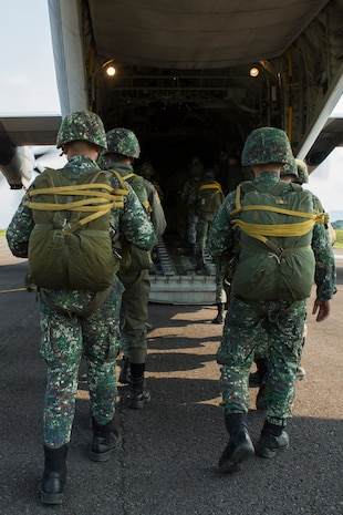 """Philippine Marines and U.S. Service members board a KC-130J """"Sumos"""", assigned to Marine Aerial Refueler Transport Squadron 152, Marine Aircraft Group 36, 1st Marine Aircraft Wing, based at Marine Corps Air Station Futenma, Okinawa, Japan, during static line jumps and High Altitude Low Opening military freefall jumps during Balikatan 2014 at Basa Air Base, Floridablanca, Republic of the Philippines, May 14, 2014. This year marks the 30th iteration of Balikatan, which is an annual Republic of the Philippines-U.S. military bilateral training exercise."""