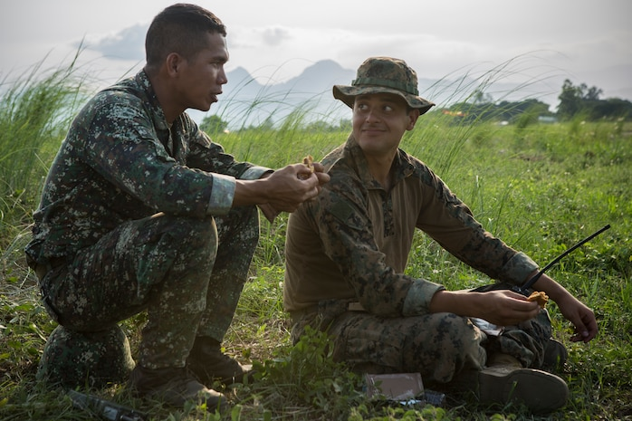 Philippine Marine Cpl. Redan Batiller, a radio point man with 62 Marine Corps Special Operations, Marine Special Operations Group, stationed at Marine Barracks Rudiardo Brown, Taguig, and U.S. Marine Corps Cpl. Kevin Goez, a field radio operator with 3rd Reconnaissance, Camp Schwab, Okinawa, Japan, share a Meal Ready to Eat while watching for the static line jumpers during during static line jumps and High Altitude Low Opening military freefall jumps during Balikatan 2014 at Basa Air Base, Floridablanca, Republic of the Philippines, May 14, 2014. This year marks the 30th iteration of Balikatan, which is an annual Republic of the Philippines-U.S. military bilateral training exercise.