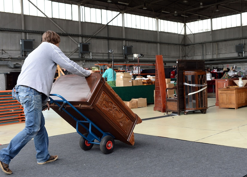 A vendor wheels a piece of furniture to his booth in Hangar 2 May 15, 2014, for the upcoming Spring Bazaar at Spangdahlem Air Base, Germany. Nearly a dozen countries are participating at the Bazaar and will sell wares that include food, furniture, artwork and home décor. (U.S. Air Force photo by Staff Sgt. Daryl Knee/Released)