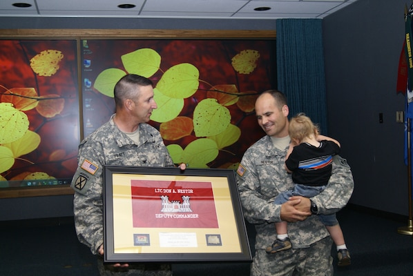 Col. Richard A. Pratt, Tulsa District Commander, presents Lt. Col. Don A. Nestor, outgoing deputy commander, with a framed Tulsa District flag during his farewell ceremony, May 15. Nestor is leaving to take command of the 8th Brigade Engineer Battalion, 2nd Brigade Combat Team, at Fort Hood, Texas.