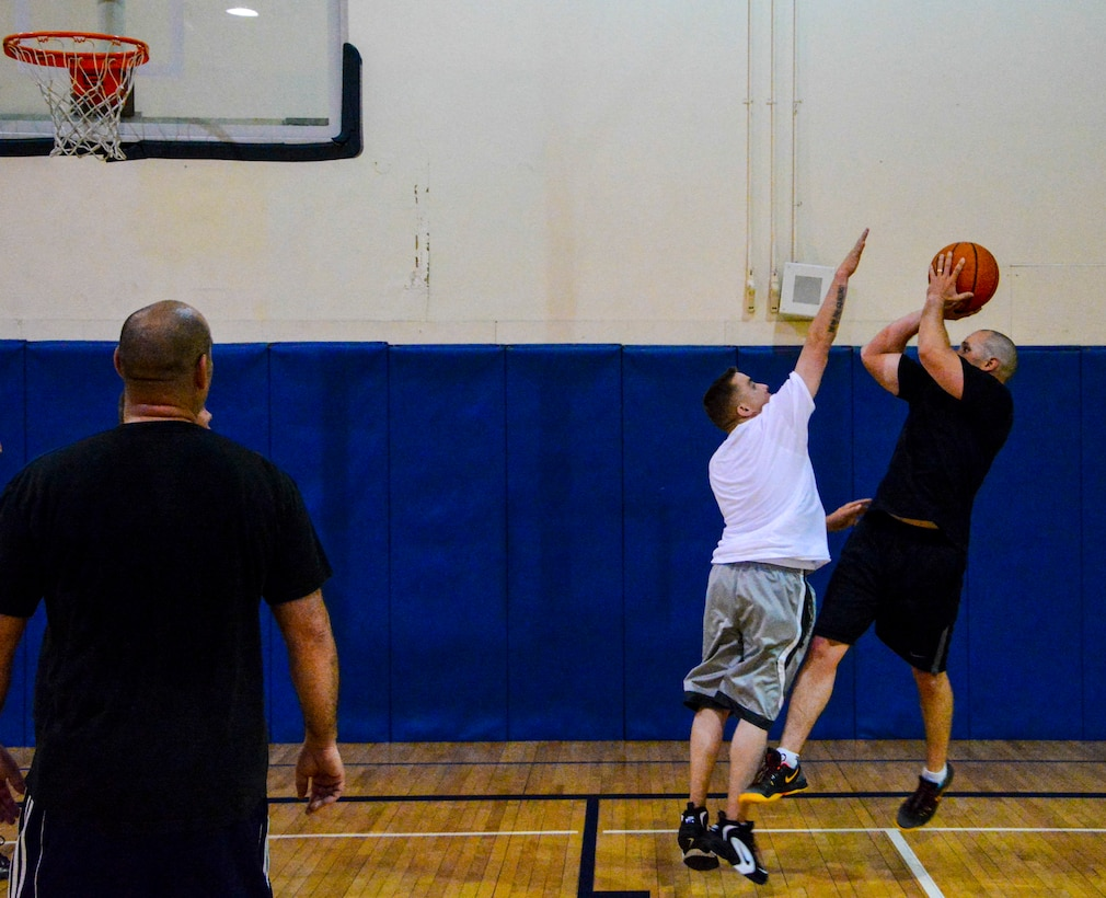 Tech. Sgt. Daniel Hose, 366th Logistics Readiness Squadron, defends the shot of Lt. Col. Todd Jensen, 366th LRS commander, during a morale basketball game at Mountain Home Air Force Base, Idaho, May 5, 2014. Sporting events bring units together and achieve morale boosts while enjoying a physical fitness session. (U.S. Air Force photo by Airman 1st Class Devin Nothstine/RELEASED)