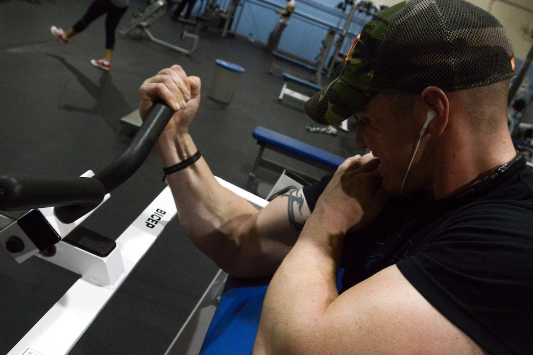 """Senior Airman Dakota Beasley, 366th Logistics Readiness Squadron vehicle operator, struggles through his last set of bicep curls at Mountain Home Air Force Base, Idaho, May 4, 2014. """"I enjoy seeing my body's limitations and breaking through those limits,"""" said Beasley. (U.S. Air Force photo by Airman 1st Class Devin Nothstine/RELEASED)"""
