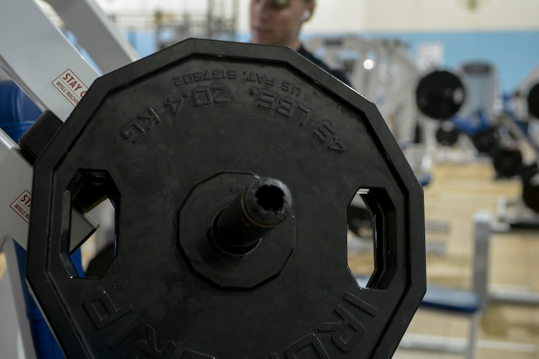 Senior Airman Dakota Beasley, 366th Logistics Readiness Squadron vehicle operator, loads weights onto a bench press machine at Mountain Home Air Force Base, Idaho, May 4, 2014. Fitness is a vital component to Airmen's readiness. (U.S. Air Force photo by Airman 1st Class Devin Nothstine/RELEASED)