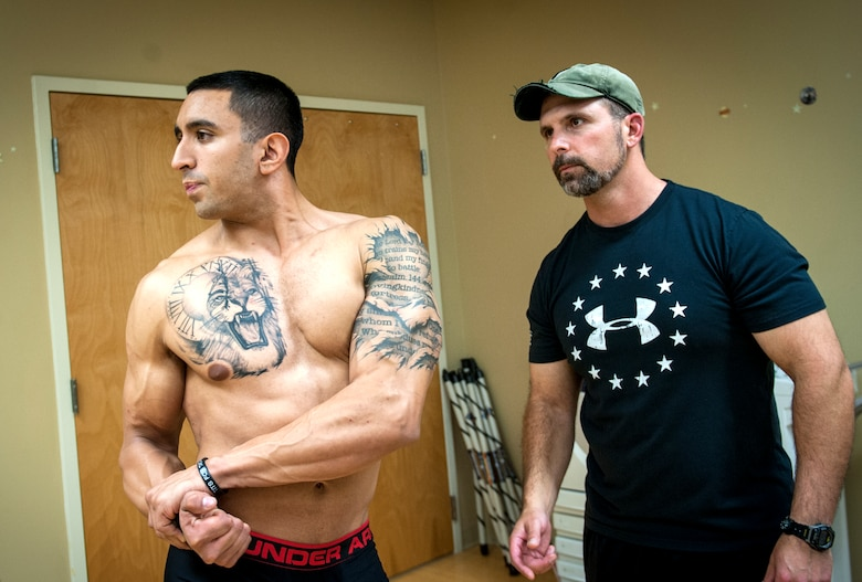 U.S. Air Force Staff Sgt. Israel Garza, left, 23d Security Forces Squadron unit trainer, practices bodybuilding poses while Chris Andruschkevich, an Aerobics and Fitness Association of America certified personal trainer, gives feedback at Moody Air Force Base, Ga., March 7, 2014. Andruschkevich, who competed in bodybuilding in his early 20s, gives advice on diet, exercise and poses to Garza in preparation for his first show scheduled for June. (U.S. Air Force photo by Senior Airman Jarrod Grammel/Released)