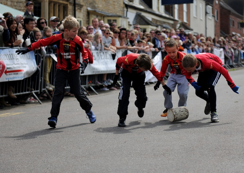 Children roll a log down a street during the 50th Annual Stilton Cheese Rolling Festival at Stilton Village, United Kingdom, May 5, 2014. The participating teams used cut telephone poles, instead of actual cheese, during the competition. (U.S. Air Force photo by Staff Sgt. Jarad A. Denton/Released)