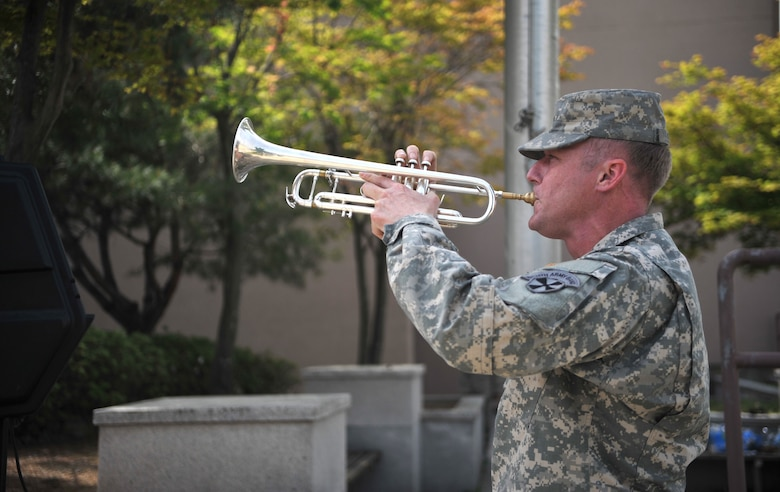 "U.S. Army Spc. Steven Leeper, 8th Army Band bugler, plays taps during the Police Week retreat ceremony at Osan Air Base, Republic of Korea, May 16, 2014. Taps is played at military funerals, memorials and can also be used as a signal for ""lights out"" on military installations. (U.S. Air Force photo/Airman 1st Class Ashley J. Thum)"