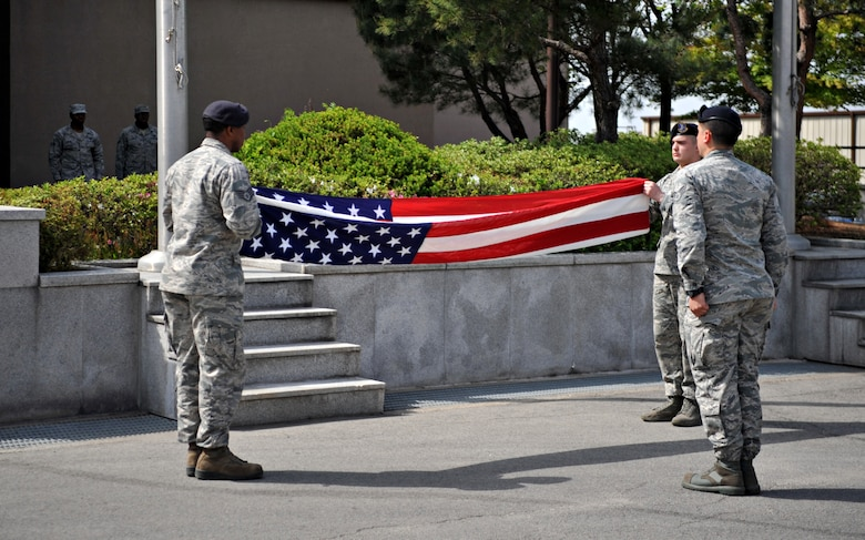 Airmen from the 51st Security Forces Squadron fold the American Flag during the Police Week retreat ceremony at Osan Air Base, Republic of Korea, May 16, 2014. Retreat traditionally signals the end of the duty day on military installations. (U.S. Air Force photo/Airman 1st Class Ashley J. Thum)