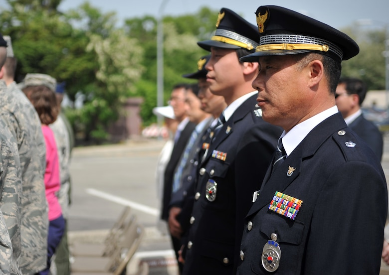 Members of the Korean National Police stand to show respect for the reading of fallen law enforcement officers' names during the Police Week retreat ceremony at Osan Air Base, Republic of Korea, May 16, 2014. The 51st Security Forces Squadron strives to maintain a strong partnership with their Korean counterparts. (U.S. Air Force photo/Airman 1st Class Ashley J. Thum)