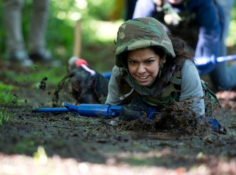Abby Sanchez, wife of U.S. Air Force Airman 1st Class Santos Sanchez, low crawls through the mud during the 52nd Security Forces Squadron National Police Week decathlon at Spangdahlem Air Base, Germany, May 14, 2014. One team of competitors was comprised entirely of spouses. The winning team was from the 52nd SFS police services section. (U.S. Air Force photo by Staff Sgt. Chad Warren/Released)