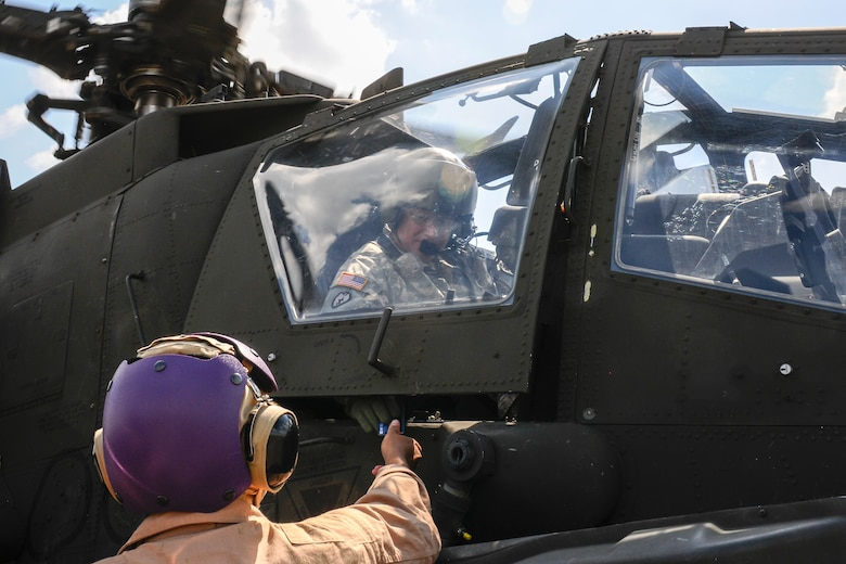 A U.S. Army AH-64 Apache pilot pays for fuel which is provided by U.S. Marines assigned to 273rd Marine Wing Support Squadron, Air Operations Company, during forward air refueling point operations at McEntire Joint National Guard Base, S.C. on May 14, 2014. Elements of the South Carolina Air and Army National Guard and the U.S. Marines conduct joint operations which are crucial to the ongoing success of operational readiness and deployments around the world.  (U.S. Air National Guard photo by Tech Sgt. Jorge Intriago/Released)