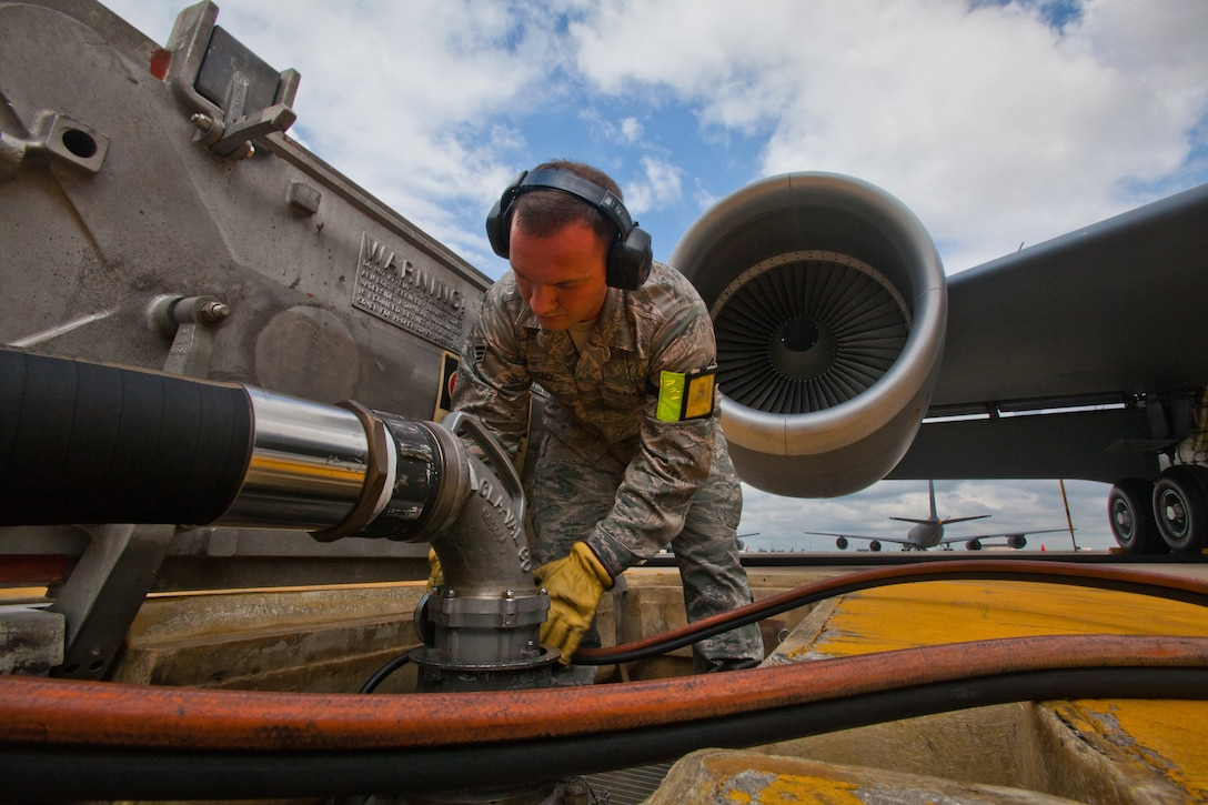 Senior Airman Victor T. Pascale, a fuels journeyman with the Petroleum, Oils and Lubricants shop, 108th Wing Logistics Readiness Squadron, connects a single point nozzle refueling hose from an R-12 hydrant-servicing vehicle to the 108th flight line's type III constant pressure system prior to refueling a KC-135R Stratotanker at Joint Base McGuire-Dix-Lakehurst, N.J., May 15, 2014. (U.S. Air National Guard photo by Master Sgt. Mark C. Olsen/Released)