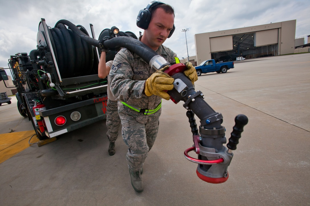 Senior Airman Victor T. Pascale, a fuels journeyman with the Petroleum, Oils and Lubricants shop, 108th Wing Logistics Readiness Squadron, carries a single point nozzle refueling hose from an R-12 hydrant-servicing vehicle to the 108th flight line to refuel a KC-135R Stratotanker at Joint Base McGuire-Dix-Lakehurst, N.J., May 15, 2014. (U.S. Air National Guard photo by Master Sgt. Mark C. Olsen/Released)