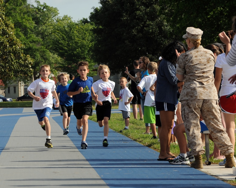 Children are cheered on during a one-mile Kids Run on Barksdale Air Force Base, La., May 17, 2014. The Kids Run is an annual fun run held on U.S. military installations around the world. (U.S. Air Force photo/Senior Airman Benjamin Gonsier)