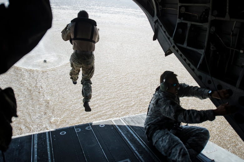 A Soldier with the 20th Special Forces Group jumps from a CH-47 Chinook helicopter for helocast training, an airborne technique used by small forces to insert into a military area of operations,  April 30, 2014, during Emerald Warrior 14 in Gulfport, Miss. Emerald Warrior is a U.S. Special Operations Command-sponsored two-week joint/combined tactical exercise designed to provide realistic military training in an urban setting. (U.S. Air Force photo/Senior Airman Jodi Martinez)
