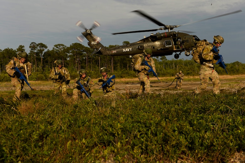 Combat controllers conduct fast-rope insertion training using a U.S. Navy HH-60H Seahawk helicopter assigned to Helicopter Sea Combat Squadron 84 at Hurlburt Field, Fla., May 2, 2014, during Emerald Warrior 2014. Emerald Warrior is a U.S. Special Operations Command-sponsored two-week joint/combined tactical exercise designed to provide realistic military training in an urban setting. (U.S. Air Force photo/Staff Sgt. Tim Chacon)