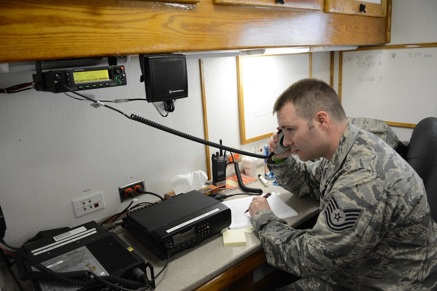 Tech. Sgt. Nathan Thrun, 128th Emergency Management program manager, listens to his radio during an exercise at the 2014 State Interoperable Mobile Communications Exercise in Oshkosh, Wis., May 15, 2014. Members of the Wisconsin National Guard tested their ability to communicate with other agencies. The 128th ARW also tested their ability to communicate with those in helicopters flying above the exercise site. (Air National Guard photo by Senior Airman Andrea F. Liechti)