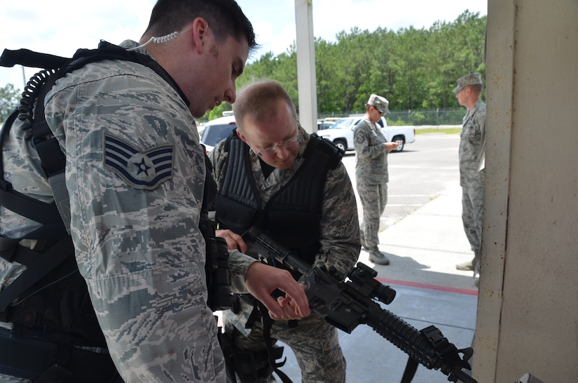 "Staff Sgt. Patrick Poss, 628th Security Forces Squadron patrolman, assists Col. Jeffrey DeVore, Joint Base Charleston commander, as the colonel clears his weapon before beginning his ""shift,"" May 14, 2014, on JB Charleston – Weapons Station. DeVore was riding along with the 628th SFS as part of a program designed to give base leaders a taste of what Airmen and Sailors do at their job centers every day. (U.S. Air Force photo/Eric Sesit)"