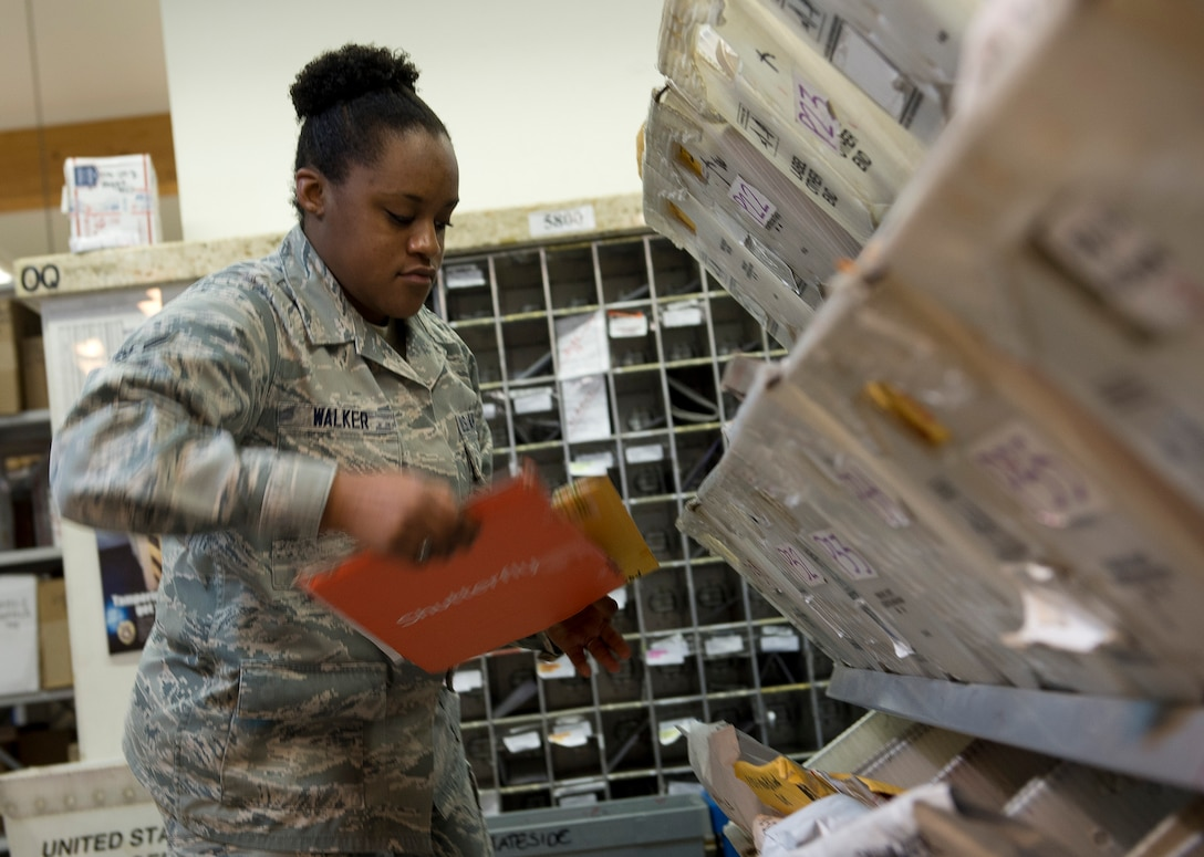 U.S. Air Force Airman 1st Class Kathryn Walker, a 52nd Communications Squadron military postal clerk from Houston, retrieves mail for customers at Spangdahlem Air Base, Germany, May 16, 2014. The post office provides a full spectrum of postal services to more than 13,000 base members. (U.S. Air Force photo by Staff Sgt. Chad Warren/Released)
