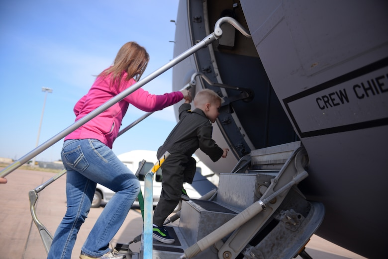 Two-year-old John Austin and his mother Kristy climb into a C-17 Globemaster III cargo aircraft May 15, 2014, at Altus Air Force Base, Oklahoma. John was diagnosed with acute lymphoblastic leukemia when he was four months old, and his parents were told that he had a 45 percent chance of surviving to age 5. (U.S. Air Force photo/Staff Sgt. Nathanael Callon)