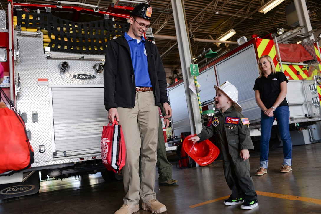 Two-year-old John Austin laughs with his father, Jason, after touring the base fire department May 15, 2014, at Altus Air Force Base, Oklahoma. The Austin family is stationed at Tinker Air Force Base, and had the opportunity to visit Altus AFB as part of the Altus Pilot for a Day program. (U.S. Air Force photo/Staff Sgt. Nathanael Callon)