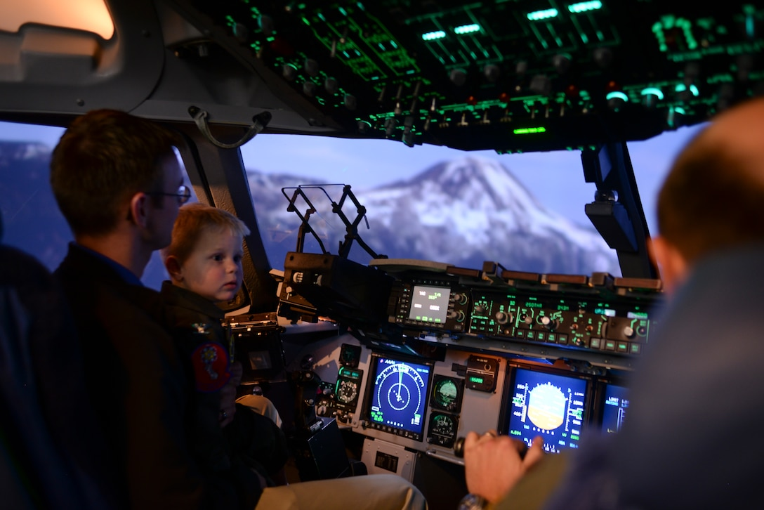 Maj. Erick Brough flies two-year-old John Austin and his father, Jason, past Mount Rainier, Wash., in a C-17 Globemaster III flight simulator May 15, 2014. The Austin family visited Altus Air Force Base and explored airplanes, fire trucks and the base air traffic control tower. (U.S. Air Force photo/Staff Sgt. Nathanael Callon)
