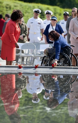 A member of the Congressional Caucus for Woman's Issues and an Army veteran place roses on the reflection pond during the Military Wreath Laying Ceremony hosted by the caucus in honor of military service women at the Woman in Military Service for America Memorial in Arlington, Virginia, May 20, 2014. The caucus recognized Sgt. Major Lanette Wright, sergeant major of the 24th Marine Expeditionary Unit, as an outstanding female Marine staff senior enlisted non-commissioned officer.