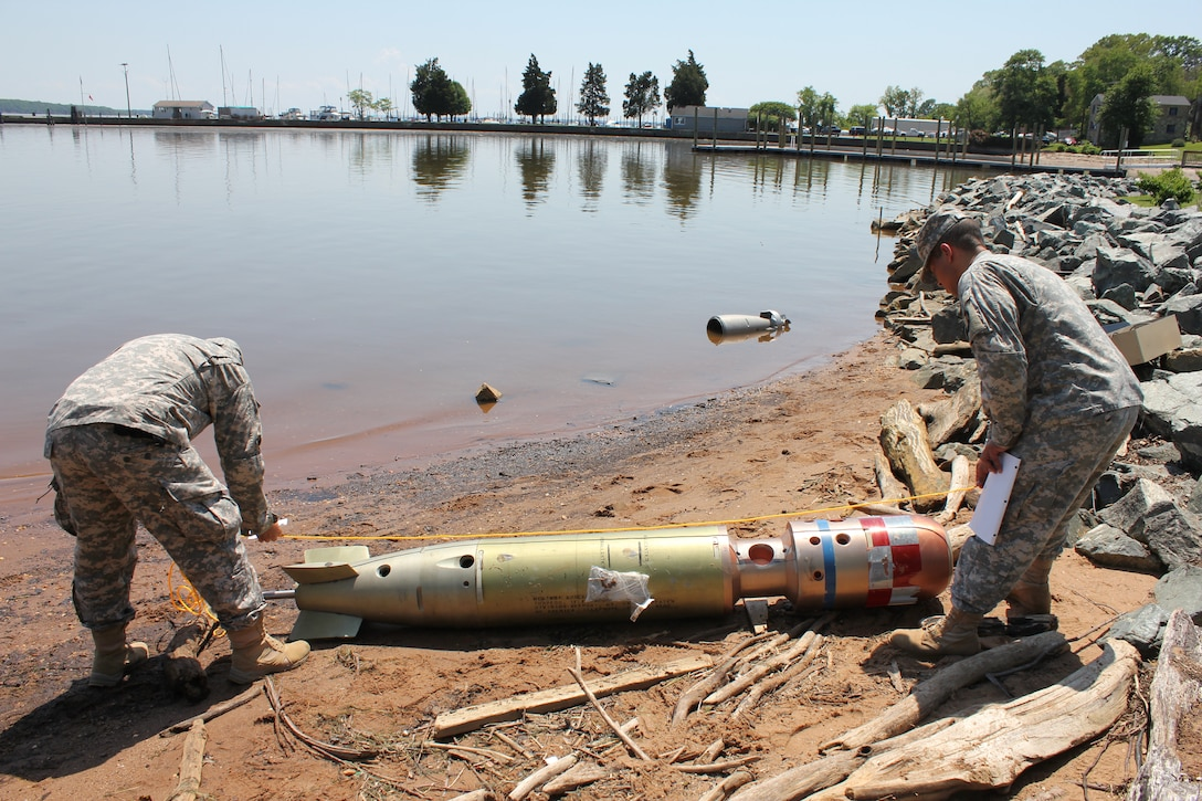 U.S. Army and Navy military members measure a water-borne IED on the shore of the Potomac River in The Town of Quantico on May 14, during the Defense Intelligence Agency's weeklong Joint Captured Materiel Exploitation Center exercise, hosted by Marine Corps Intelligence Activity aboard Marine Corps Base Quantico from May 12 to 16.