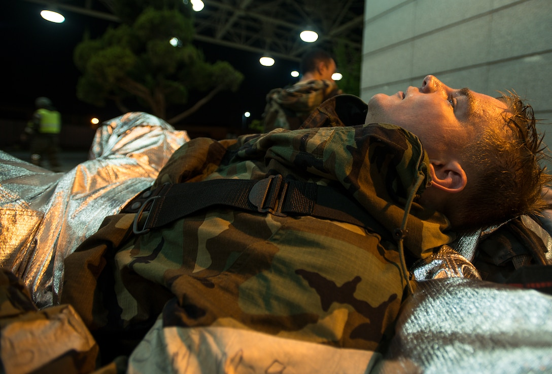 Senior Airman Robert McCallon, 51st Civil Engineer Squadron firefighter, rests after completing a simulated mass casualty exercise May 6, 2014, at Osan Air Base, Republic of Korea. The firefighters are constantly trained on various techniques, but during wing exercises have the added challenge of wearing their MOPP gear. (U.S. Air Force photo by Staff Sgt. Jake Barreiro)