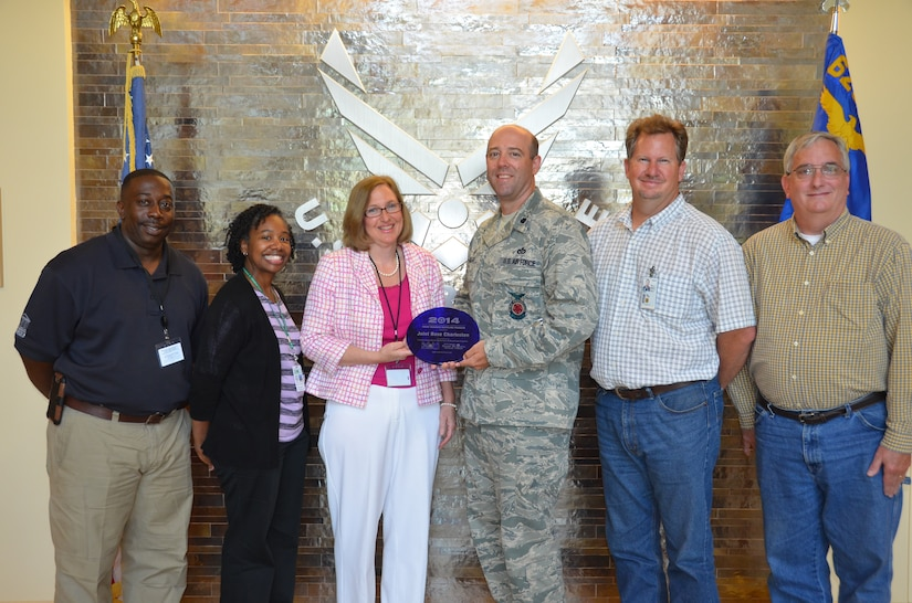 Lt. Col. Patrick Miller, 628th Civil Engineer Squadron commander accepts a plaque from Christine Sanford- Coker, DHEC Area Director LowCountry Environmental Health Services, Charleston Office May 20, 2014, at Joint Base Charleston, S.C. Joint Base Charleston was honored for its comprehensive recycling program that resulted in earning more than $268,000 from the sale of recyclable materials and a reduction in disposal costs of almost $7,000. In addition, the base has a green procurement policy that requires products and services meet high environmental standards regardless of procurement method or purchase value. Along with Miller and Sanford-Coker are (left to right) Edgar Jennings, Charleston County Environmental Management superintendent, Stacey Washington, DHEC Environmental Engineering Associate, Alan Moyer, 628th CES Solid Waste program manager and Dennis Bates, 628th CES Environmental Project Specialist. (U.S. Air Force photo/Eric Sesit)