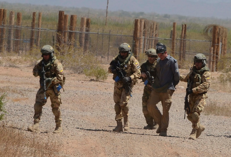 Members of a Multinational Search and Rescue Team  capture an opposition force member during a training mission in Exercise ANGEL THUNDER on May 16, 2014 at the Florence Military Reservation, Ariz. ANGEL THUNDER 2014 is the largest and most realistic joint service, multinational, interagency combat search and rescue exercise designed to provide training for personnel recovery assets using a variety of scenarios to simulate deployment conditions and contingencies. Personnel recovery forces will train through the full spectrum of personnel recovery capabilities with ground recovery personnel, air assets, and interagency teams. (U.S. Air Force photo by Staff Sgt. Adam Grant/Released)