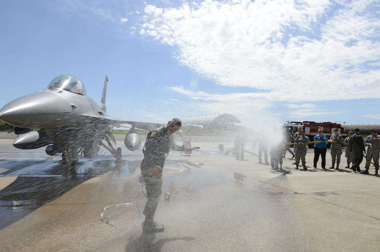 Spangdahlem community members spray U.S. Air Force Col. David Julazadeh, 52nd FW commander, with water after his final flight in an F-16 Fighting Falcon fighter aircraft May, 20, 2014, at Spangdahlem Air Base, Germany. Members throughout the wing attended Julazadeh's final flight ceremony.  (U.S. Air Force photo by Staff Sgt. Christopher Ruano/Released)
