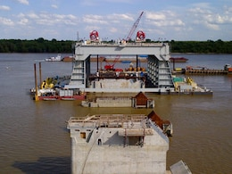 The catamaran barge (background) is used to set shells that comprise the dam. 