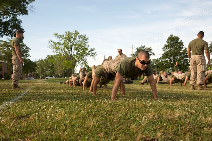 Lance Cpl. Louis Huntoon, a clerk with Alpha Company,, leads the way in Alpha Company's squad pushup during the Super Squad event at HQSPTBn's Commanders Cup Challenge field meet aboard Marine Corps Base Camp Lejeune, May 15. The Super Squad was considered the toughest event of the competition.