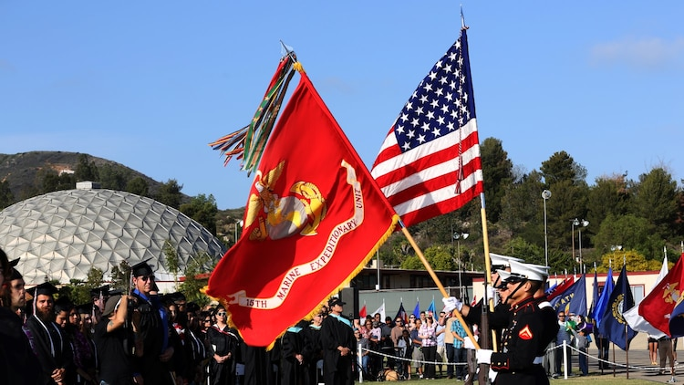 Corporal Justin G. Rush, embarkation specialist, 15th Marine Expeditionary Unit, presents the Organizational Colors during a commencement ceremony at Palomar College campus in San Marcos, Calif., May 20, 2014. Rush, 20, is from Tacoma, Wash. (U.S. Marine Corps photo by Cpl. Emmanuel Ramos/Released)