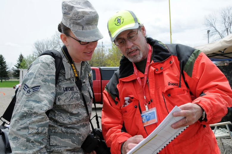 Air Force Senior Airman Andrea Liechti, a photojournalist with the 115th Fighter Wing of the Wisconsin Air National Guard, is briefed by Mr. John Maggitti, an ametuer radio operator participating in SIMCOM 2014 at Sunnyview Expo Center in Oshkosh, Wis. May 15, 2014. SIMCOM (State Interoperable Mobile Communications) is a functional exercise designed to test the interoperability of federal, state, county, tribal, volunteer, private organizations and defense communications and data sharing. Air National Guard photo by Tech. Sgt. Todd Pendleton (Released)