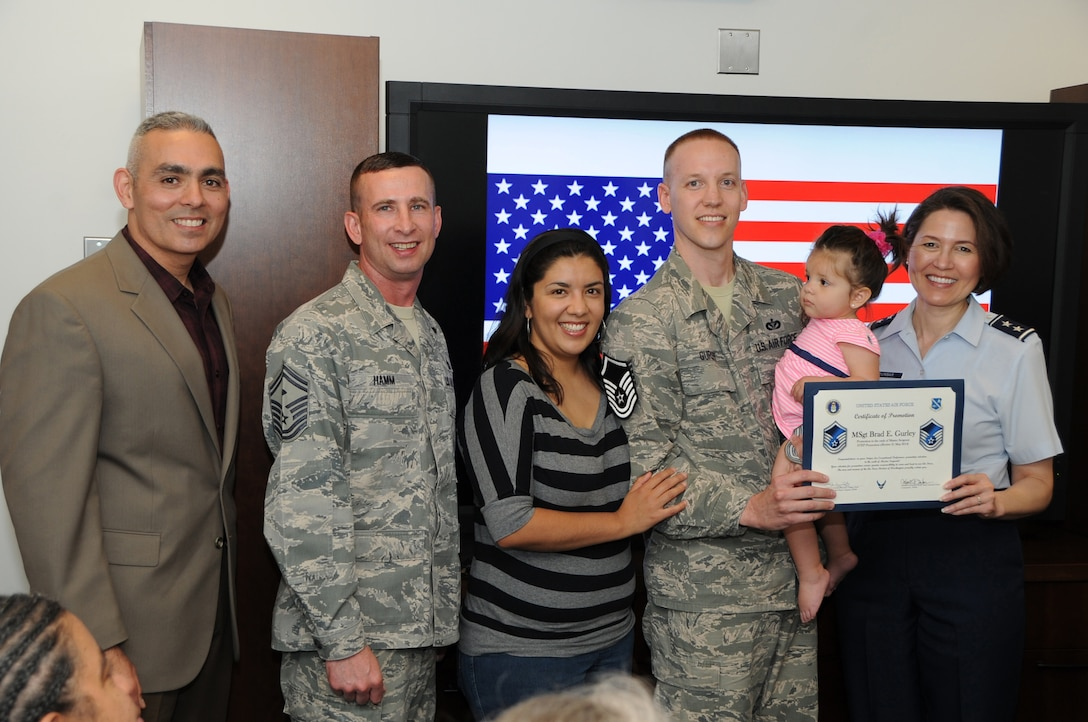 Air Force District of Washington Commander Maj. Gen. Sharon K. G. Dunbar, AFDW Command Chief Master Sgt. Jose LugoSantiago and AFDW First Sergeant Senior Master Sgt. Johnny Hamm present a Stripes for Exceptional Performers promotion for the rank of master sergeant to Tech. Sgt. Brad Gurley as he stands with wife Nicole and daughter Gabriela at Joint Base Andrews, Md., May 21, 2014. A STEP promotion is used by commanders to recognize exceptional performers by immediately awarding them the next rank. Gurley is the executive assistant to the AFDW command chief. (U.S. Air Force photo/Staff Sgt. Matt Davis)